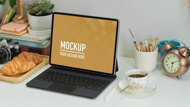 Photo recadrée de bureau à domicile avec tablette numérique, fournitures, croissant et café