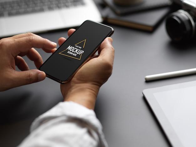 Photo recadrée d'un entrepreneur masculin à l'aide d'une maquette de smartphone sur une table de travail noire
