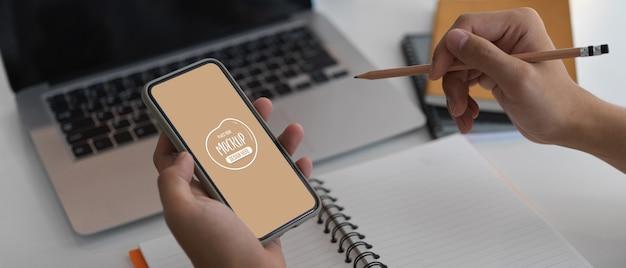 Photo recadrée d'un homme d'affaires travaillant sur son idée avec une maquette de smartphone tout en l'écrivant