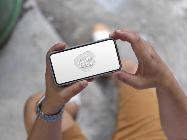 Photo recadrée de jeune homme tenant une maquette de smartphone horizontal alors qu'il était assis en plein air