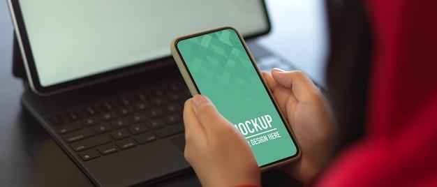 Photo recadrée de mains féminines tenant une maquette de smartphone tout en travaillant avec une maquette de tablette