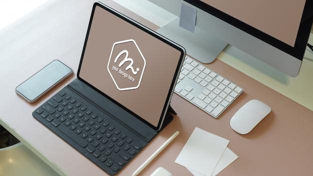 Photo recadrée d'une maquette de tablette numérique sur un bureau d'ordinateur avec smartphone et accessoires