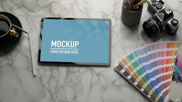Photo recadrée de maquette de tablette sur table en marbre avec appareil photo, fournitures et espace de copie
