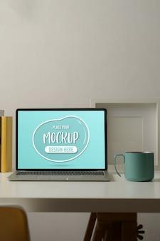 Photo recadrée de table de travail avec maquette d'ordinateur portable, tasse, maquette de cadre et fournitures dans la salle de bureau