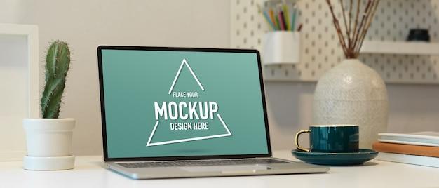 Photo recadrée de table de travail avec maquette d'ordinateur portable