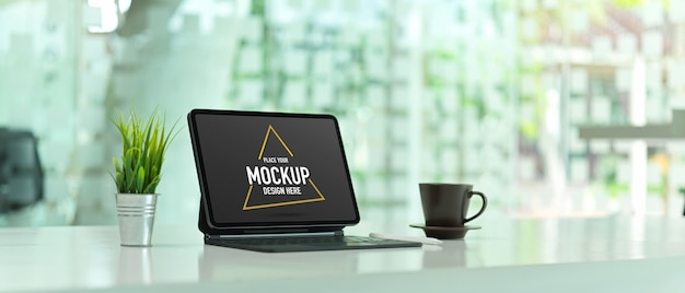 Photo recadrée de table de travail avec maquette de tablette numérique