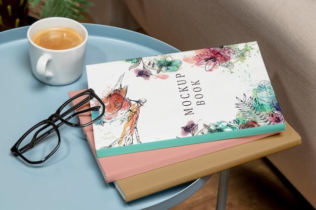 Pile de livres à angle élevé maquette sur table basse avec des lunettes