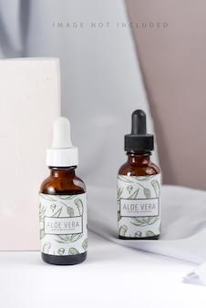 Pipette avec goutte d'huile cosmétique au-dessus d'une bouteille brune maquette avec boîte et ombre
