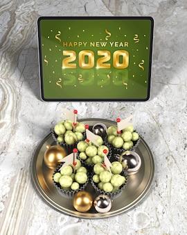 Plateau avec chocolat à côté d'une tablette avec message du nouvel an
