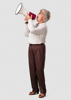 Plein corps femme senior excitée et euphorique, criant avec un mégaphone