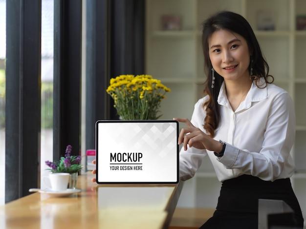 Portrait de femme montrant une maquette de tablette numérique