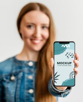 Portrait de femme tenant un smartphone maquette