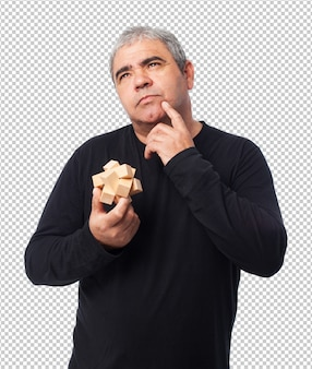 Portrait d'un homme mûr essayant de résoudre un puzzle
