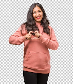 Portrait de jeune femme indienne fitness faisant un coeur avec les mains, exprimant le concept d'amour et d'amitié, heureuse et souriante