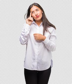 Portrait de jeune femme indienne pensant et levant les yeux, confus à propos d'une idée, serait en train de chercher une solution