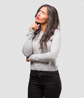 Portrait de jeune femme indienne pensant et levant les yeux, confuse à propos d'une idée