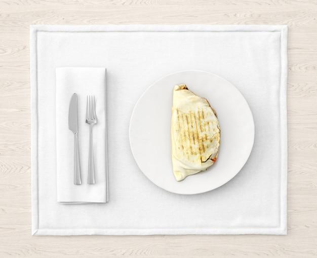 Poulet sur une plaque blanche avec des couverts