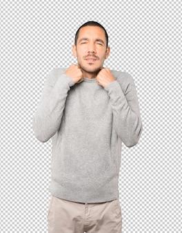 Préoccupé jeune homme faisant un geste d'avoir froid