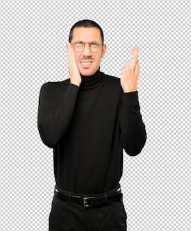 Préoccupé jeune homme faisant un geste de doigts croisés