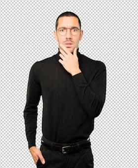 Préoccupé jeune homme posant sur fond