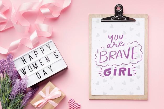Presse-papiers à côté de la lightbox avec message de la journée de la femme heureuse