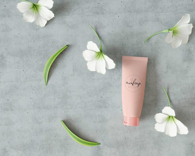 Produit cosmétique sur surface de ciment avec des fleurs