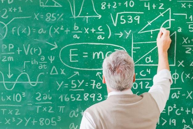 Professeur écrit des formules mathématiques à bord