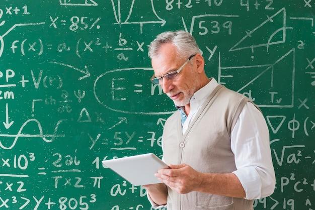 Professeur de mathématiques tenant une tablette blanche