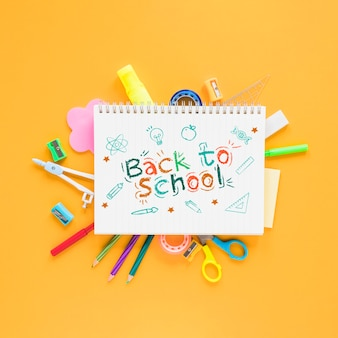 Retour aux fournitures scolaires sur fond jaune