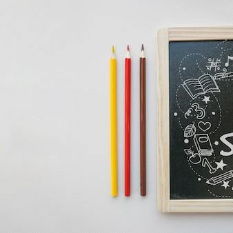 Retour à la maquette de l'école avec l'ardoise à côté des crayons