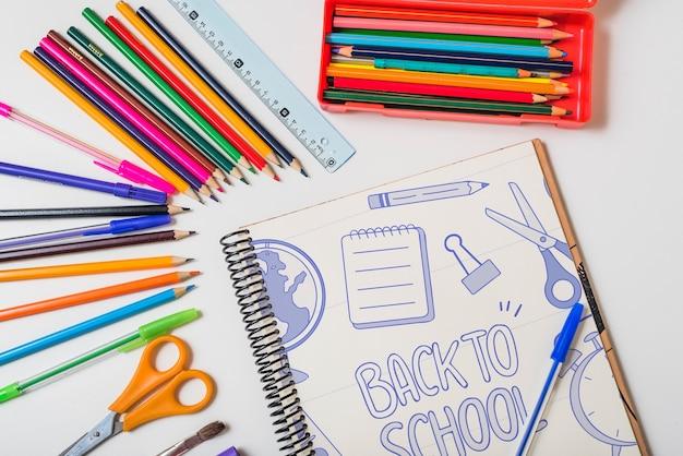 Retour à la maquette d'école avec carnet et crayons