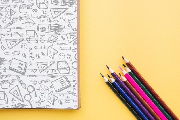 Retour à la maquette de l'école avec une couverture de cahier et des crayons