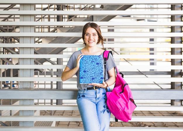 Retour à la notion d'école avec une fille présentant une couverture de livre