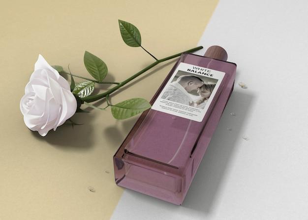 Rose blanche à côté de la bouteille de parfum