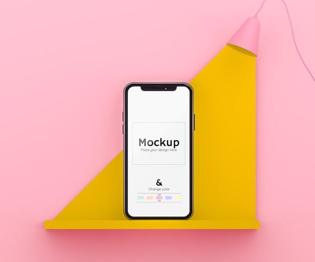 Scène 3d rose et jaune avec une lampe éclairant un téléphone portable sur une étagère et une couleur modifiable