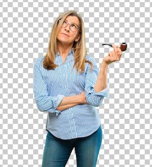 Senior belle femme avec une pipe vintage de fumée