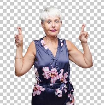 Senior femme cool croise les doigts souhaitant la chance, avec une expression pleine d'espoir, empressée et excitée.