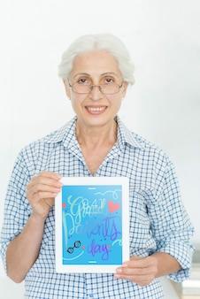 Senior femme tenant une maquette de tablette