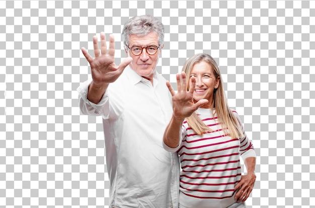 Senior mari et femme souriants et satisfaits et heureux, comptant le numéro cinq