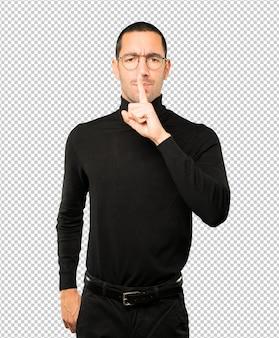 Sérieux jeune homme demandant le silence en faisant des gestes avec son doigt