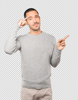 Sérieux jeune homme faisant un geste de concentration