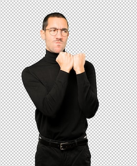 Sérieux jeune homme faisant un geste de force