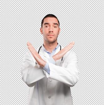Sérieux jeune médecin faisant un geste d'interdiction