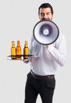 Serveur avec des bouteilles de bière sur le plateau criant par mégaphone