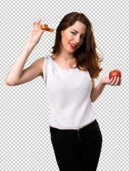 Slim femme avec un ruban à mesurer et tenant une pomme