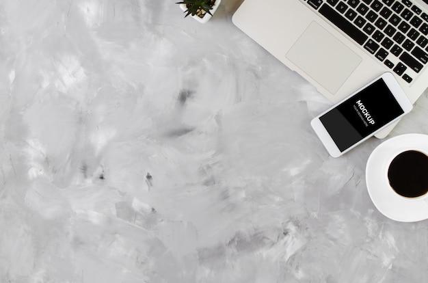 Smartphone blanc avec écran blanc noir sur le bureau avec ordinateur portable et tasse de café