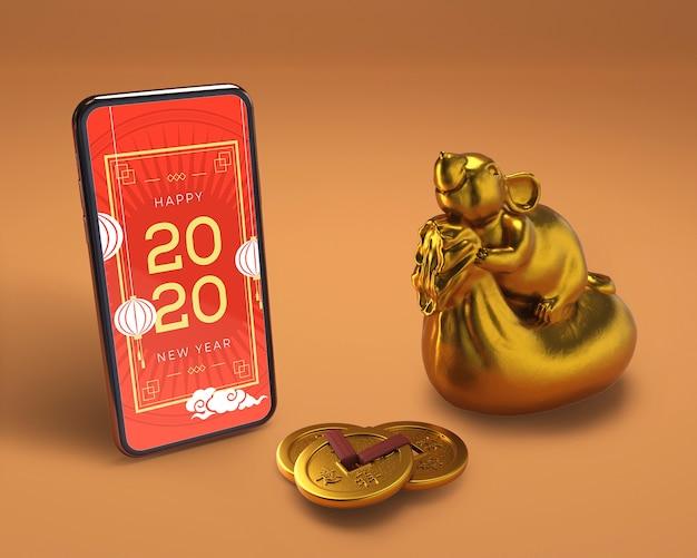 Smartphone à côté de la statue dorée du nouvel an