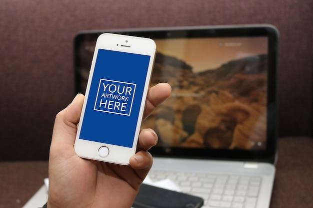 Smartphone avec écran vert en main avec fond d'ordinateur portable