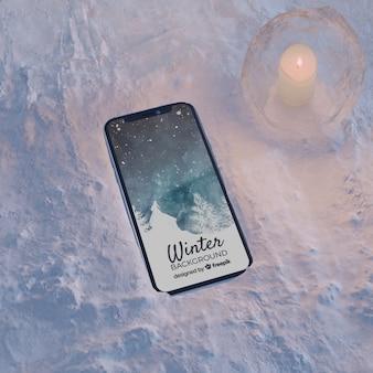 Smartphone sur la lumière de bloc de glace par la bougie