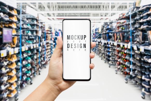Smartphone maquette avec des chaussures de sport sur des étagères en boutique
